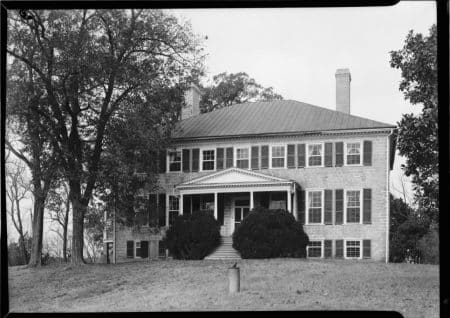 A black and white photograph of an old house with a columned overhang.