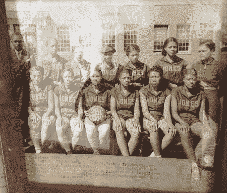 "An old photograph of a basketball team of young African American girls. The girls are seated in two rows and wear matching sweatshirts that read ""Jones."" The girl in the center of the first row holds a basket ball with ""'38 champs"" written on it."