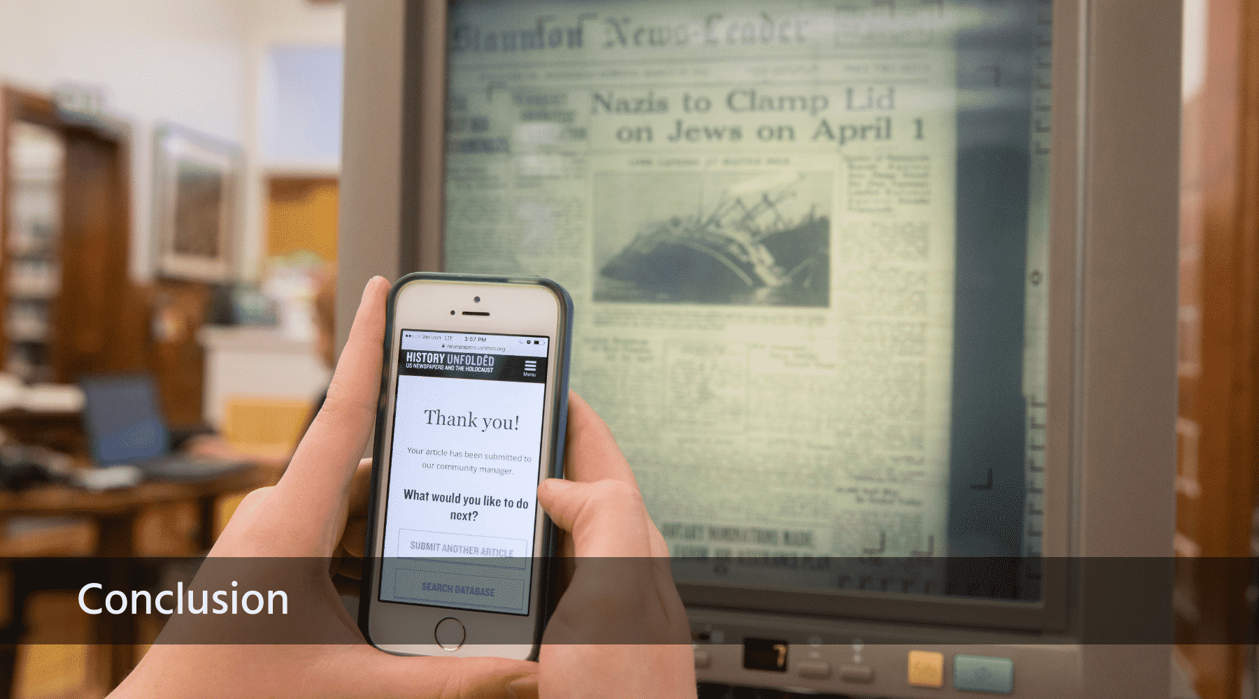 A close up image of a smart phone in front of a microfilm reader, demonstrating the app used to upload newspaper articles for the exhibition.