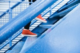 A person with orange sneakers climbing blue stairs.