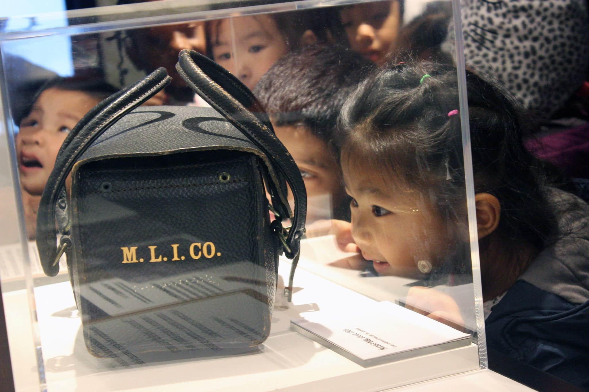 A little girl looks at a medical bag in a display case.