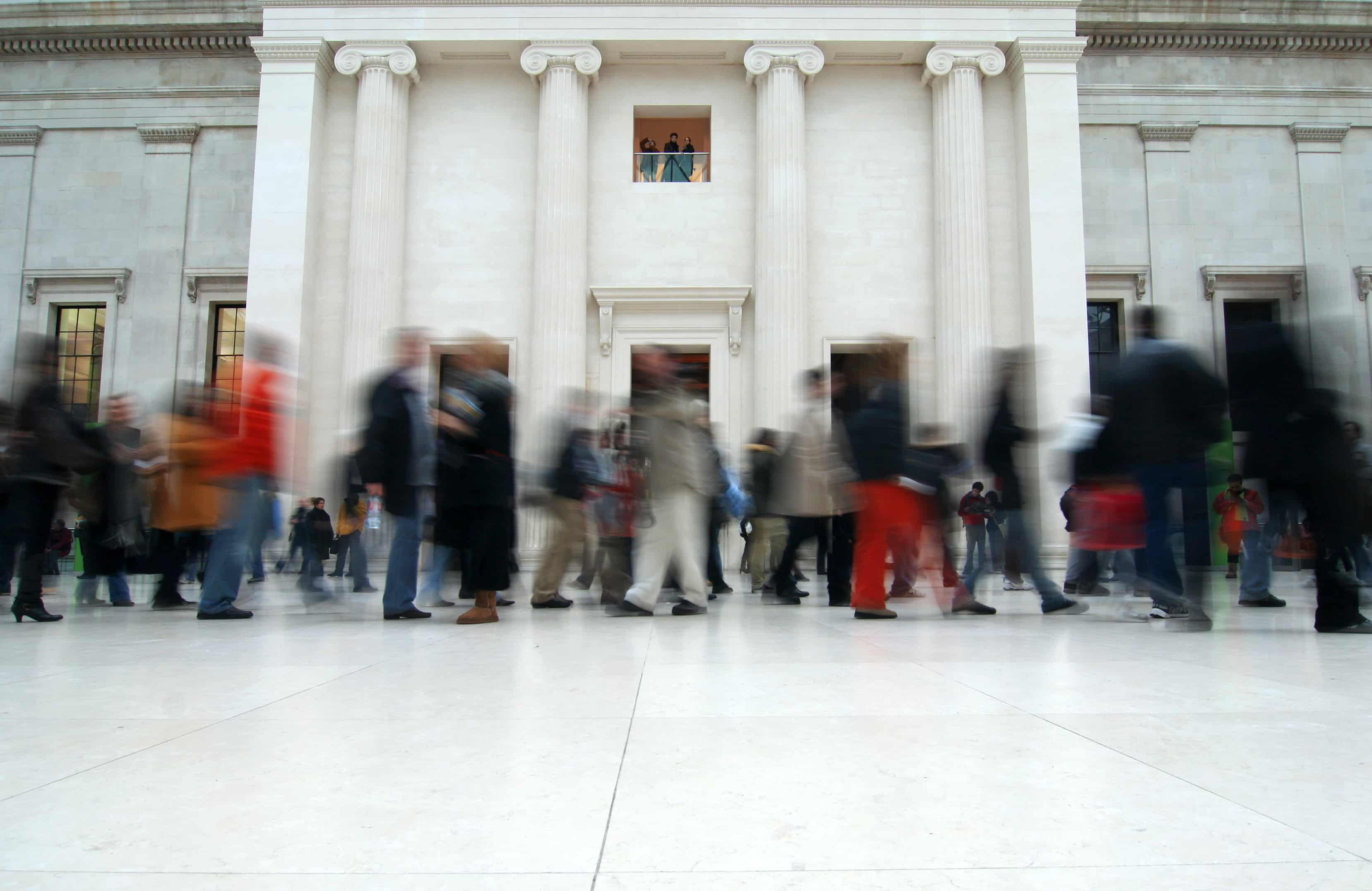 A blurry crowd of people walking in front of a white building with columns.
