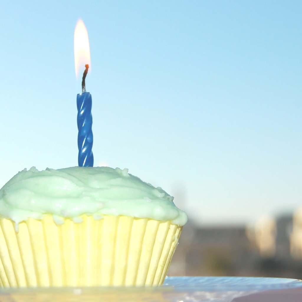 Image of a cupcake with green frosting and one burning candle