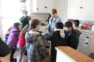 A DHM volunteer explains to a group of second-graders how to make butter.