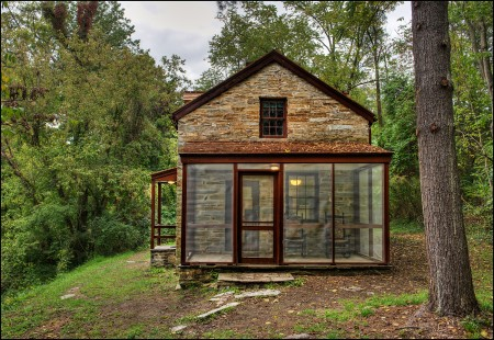 Lockhouse 10, in Cabin John, MD, features a screened-in porch and is nestled in the trees above the canal and towpath.