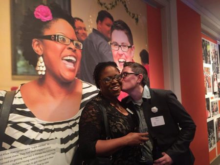 Brittany Jones and Alice Hoenigman in front of their prominent place in the A Visual Journey: From AIDS to Marriage Equality exhibition celebrating LGBT history in Indiana