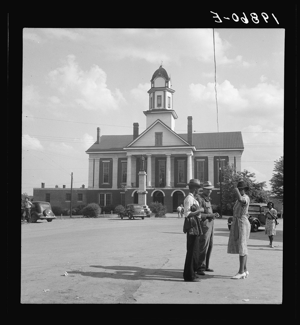Dorothea Lange's 1939 photograph captures the color line at work in Pittsboro, North Carolina. During the Jim Crow-era, Confederate monuments in courthouse squares throughout the South symbolized the connection between the Civil War and racial inequality. Library of Congress, Prints and Photographs Division
